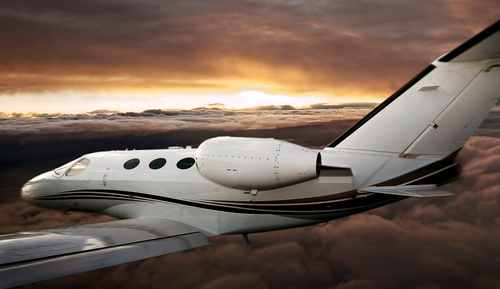 Private Jet flying during sunset